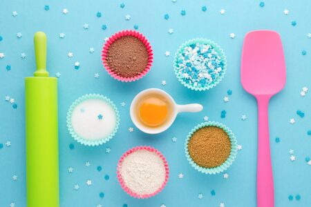 ingredients for baking and kitchen tools on blue background, flat lay