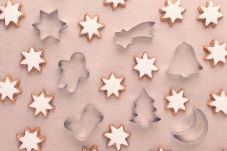 christmas background with cookie cutter and star cookies on baking paper