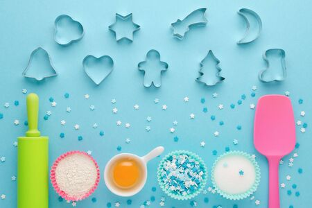 ingredients for baking and kitchen tools with cookie cutter on blue background, flat lay Zdjęcie Seryjne