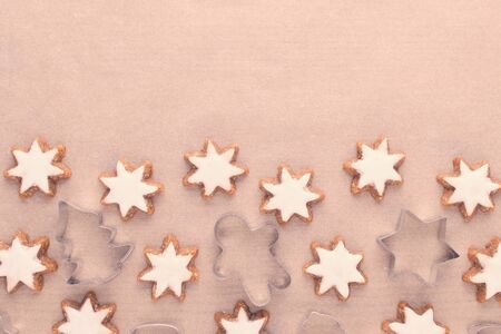 christmas background with cookie cutter and star cookies on baking paper, copy space