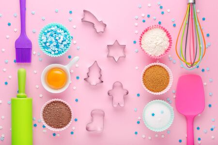 ingredients for baking and kitchen tools with cookie cutter on pastel pink background, flat lay