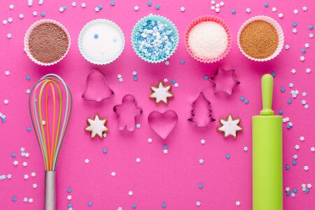 ingredients for baking and kitchen tools with cookie cutter on pink background, flat lay