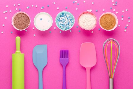 ingredients for baking and kitchen tools on pink background, flat lay