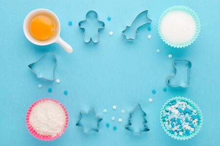 baking ingredients and cookie cutter on blue background, flat lay