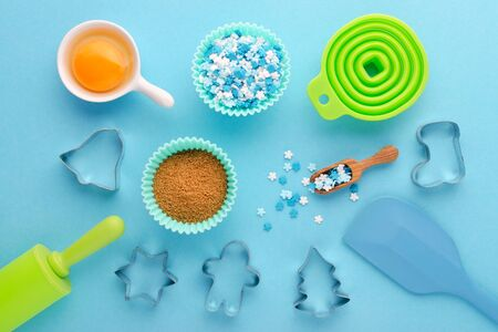 ingredients and kitchen tools for baking with cookies cutter on blue background, flat lay