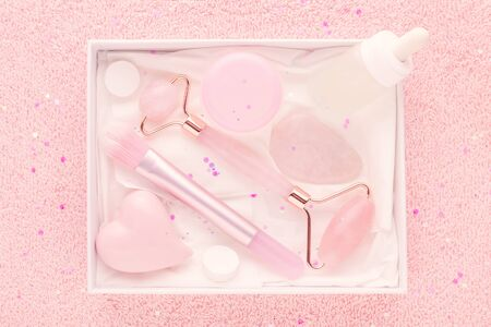 beauty box with rose quartz jade roller and stone, face serum and brush on pastel pink background, flat lay