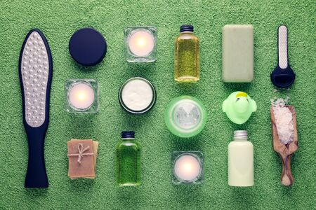wellness and spa products, laser feet grater, cream, lotion, soap, pink salt and candle on green towel Stok Fotoğraf
