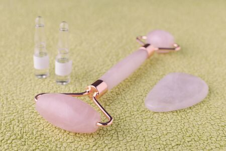 rose quartz facial roller, massage stone and face serum in ampoules Stok Fotoğraf