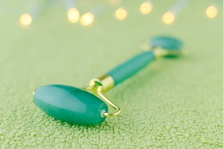 real jade facial roller on green background with bokeh