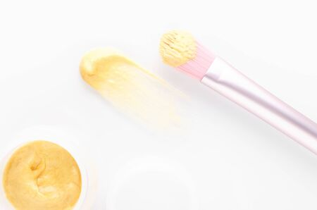 golden facial beauty mask with a brush on white background, above, selective focus