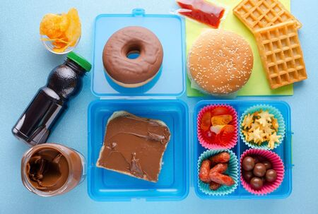 Lunch box with unhealthy food on blue background, flat lay