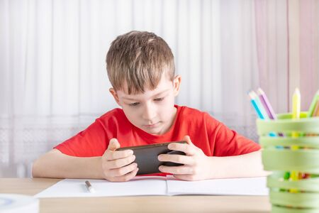 schoolboy playing on smartphone and does not do homework