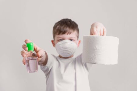coronavirus concept, boy with mask holds toilet paper and antibacterial gel