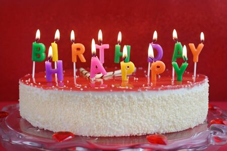 birthday cake with candles on red party background, closeup