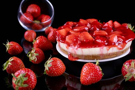 cheesecake with strawberry and fresh berries on black background, closeup