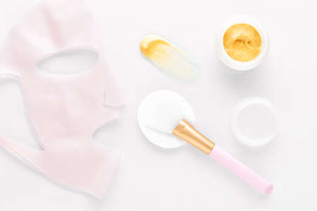golden facial cream mask with a brush and silicone beauty mask on white Stok Fotoğraf