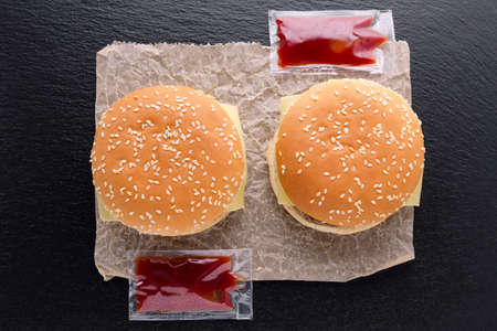 top view of two tasty homemade burgers on paper and ketchup on black background Stok Fotoğraf