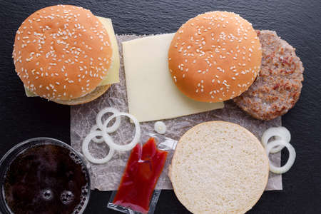 preparation of homemade burger on black background, flat lay