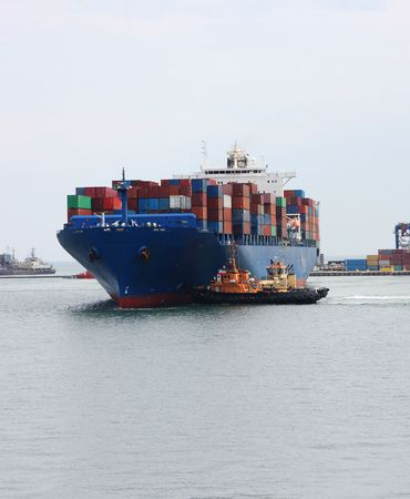 tugboats pulling a container vessel photo