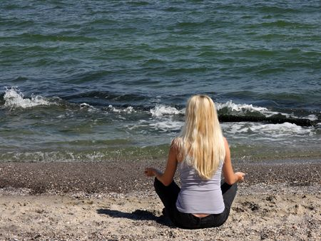 woman during meditation on the beach photo