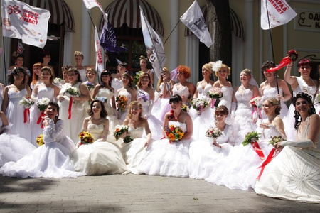 "ODESSA,UKRAINE – MAY 29: Annual event "" Bride Parade"". Happy excited participants in fiancee's gowns take part in celebration of marriage and romance Bride Parade on May 29 , 2011 in Odessa,Ukraine  Stock Photo - 9638278"