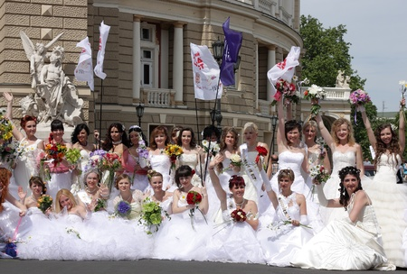 "ODESSA,UKRAINE – MAY 29: Annual event "" Bride Parade"". Happy excited participants in fiancee's gowns take part in celebration of marriage and romance Bride Parade on May 29 , 2011 in Odessa,Ukraine  Stock Photo - 9638280"