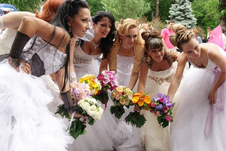 """ODESSA,UKRAINE – MAY 27: Annual event """" Bride Parade"""". Happy excited participants in fiancee's gowns take part in celebration of marriage and romance Bride Parade on May 27, 2012 in Odessa,Ukraine"""