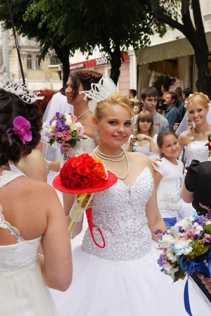 """ODESSA,UKRAINE – MAY 27: Annual event """" Bride Parade"""". Happy excited participants in fiancee's gowns take part in celebration of marriage and romance Bride Parade on May 27, 2012 in Odessa,Ukraine Stock Photo - 13795628"""