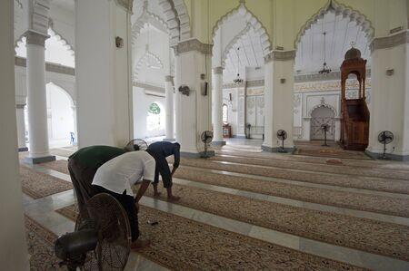 GEORGETOWN, PENANG - MARCH 10: A group of people praying inside Kapitan Keling Mosque, Penang on March 10, 2013.