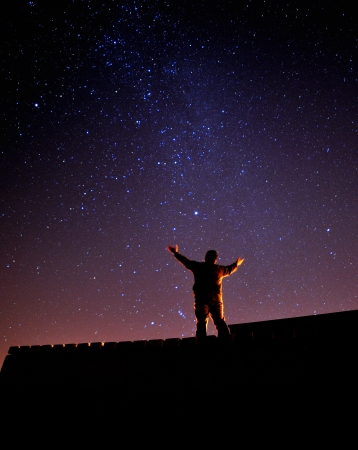 A man gazing upon the stars during one clear night Stock Photo