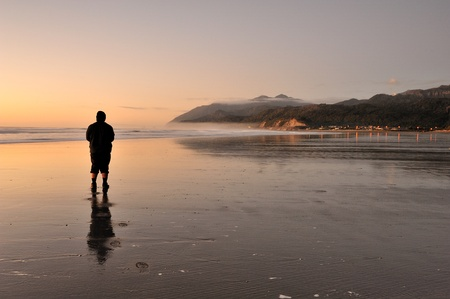Man walking alone alongside the beach during evening