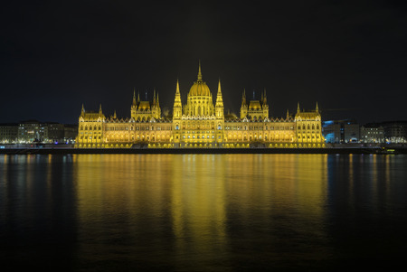 The view of Hungarian Parliament Building beside Danube River at Budapest, Hungary during night.