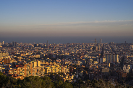 The view of the city of Barcelona from the hill in the suburb area during evening before sunset with clear sky and patchy clouds