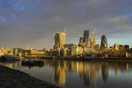 The view of the skyscrapers of City of London with its reflection on the Thames River in London, United Kingdom during a cloudy morning.