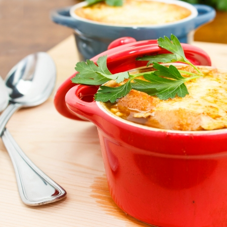 French onion soup in red and blue pots