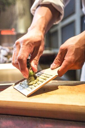 grating: Grating wasabi on a cutting board