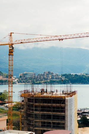 construction project: Construction of a multistory building in Budva, Montenegro. Builders are building a house. Crane working at a construction site. Sticks reinforcement of concrete. Stock Photo