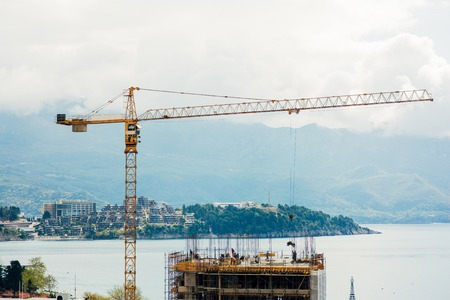 Construction of a multistory building in Budva, Montenegro. Builders are building a house. Crane working at a construction site. Sticks reinforcement of concrete. Stock Photo