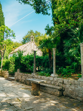 Lush vegetation, paved passageway and a pavilion at the arboretum in Trsteno, Croatia.