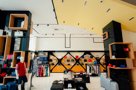 Interior of a clothing store. Clothing for men and women on the store shelves. Shopping hall end clothing store.
