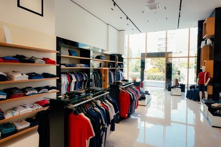 Wnętrze sklepu odzieżowego. Odzież damska i męska na sklepowych półkach. Sklep odzieżowy kończący halę handlową.