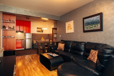 contemporary living room: Black leather sofa in the apartment. Interior living room.