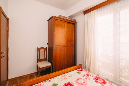 living room window: The bedroom in the apartment. Bed, wardrobe, bedside tables in the bedroom of the apartment. Stock Photo