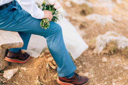 leather texture: Brown shoes on male legs. The groom in a blue pants. Stock Photo