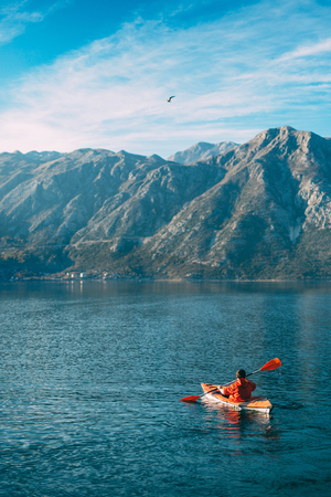 Kayaks in the lake. Tourists kayaking on the Bay of Kotor, near the town of Perast in Montenegro. Aerial Photo drone. Stock Photo