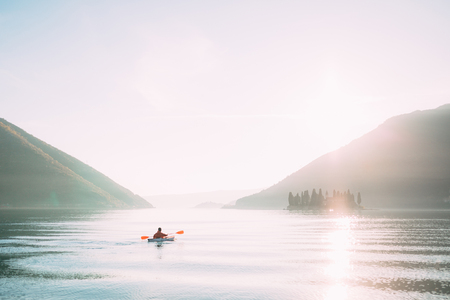 Kayaks in the lake. Tourists kayaking on the Bay of Kotor, near the town of Perast in Montenegro. Aerial Photo drone. 스톡 콘텐츠