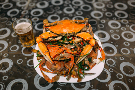 Mount cooked blue crabs in a bowl on a table with beer.