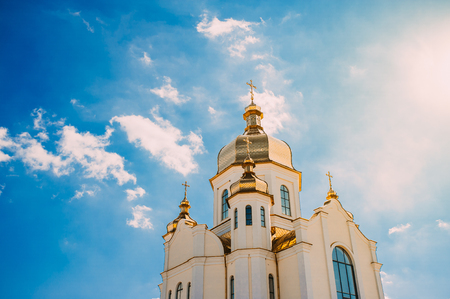 White church with golden domes against a blue sky with clouds.