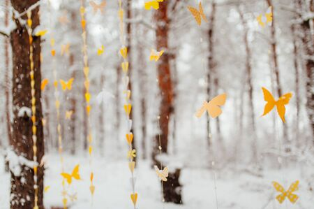 butterfly isolated: garland of paper butterflies. Against the background of a snow-covered forest.