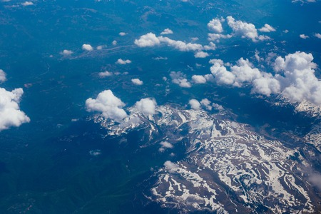 window view: Snow-covered mountains of the plane in Montenegro